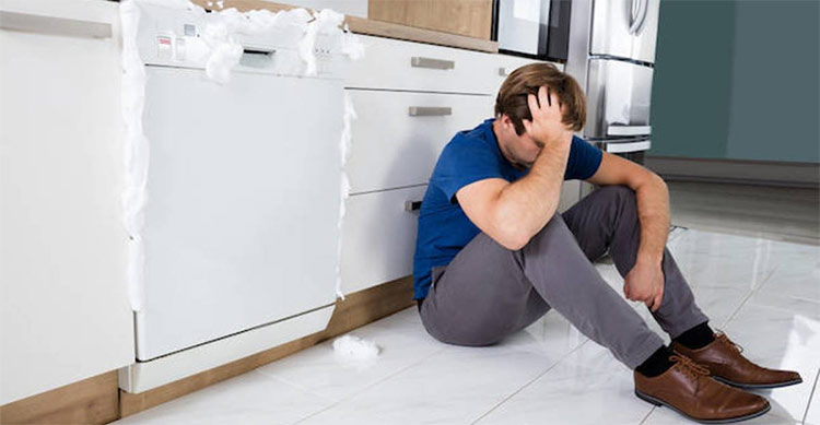 picture of a man sitting beside a broken dishwasher