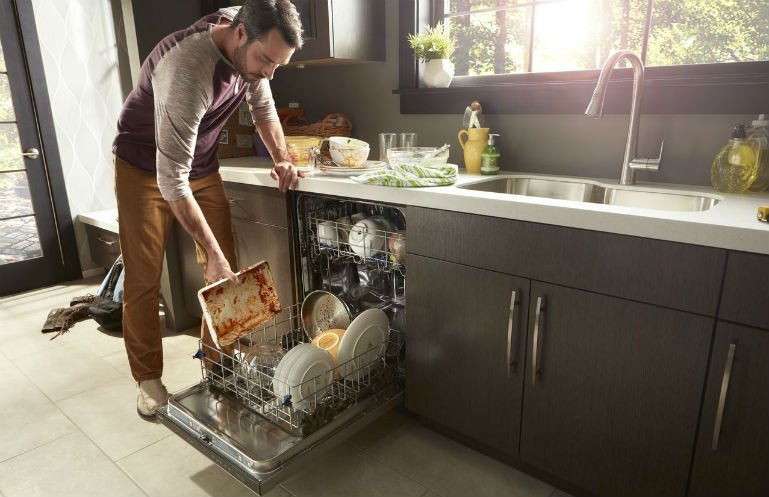 man loading dirty dishes into the dishwasher